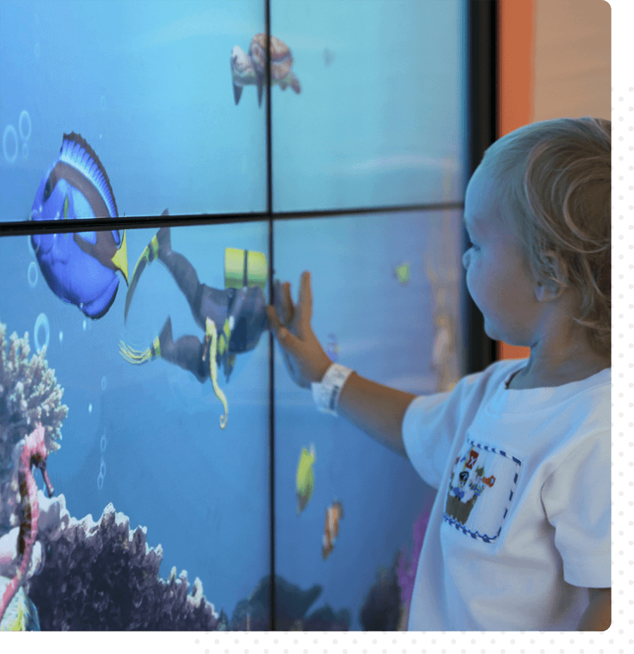 A child touches an interactive digital wall at Vidant Children's Hospital.