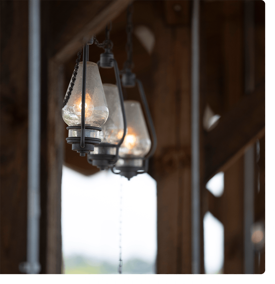 3 lanterns handing outside under a wood pavilion