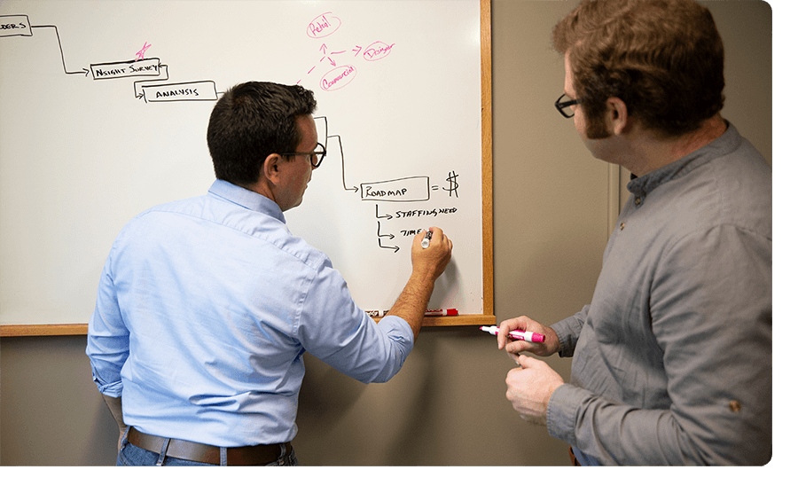 Two male employees draw something on whiteboard.