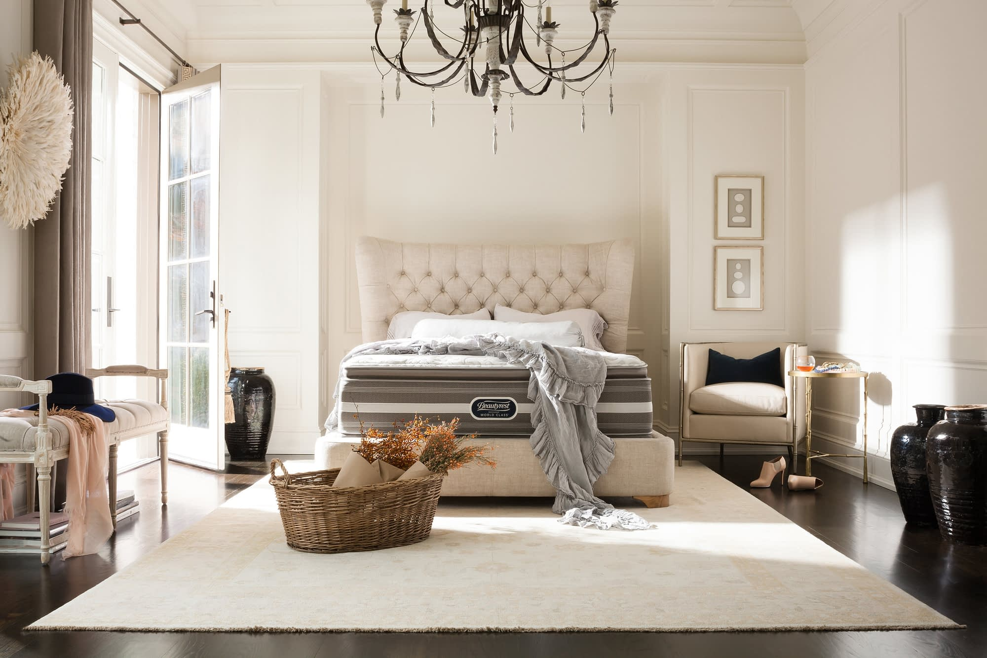 A large bedroom with beige walls, a beige carpet, and beige bed. The bed has a Beautyrest mattress on it.