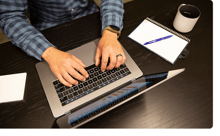 Man working on a laptop with a notepad and coffee cup beside him.