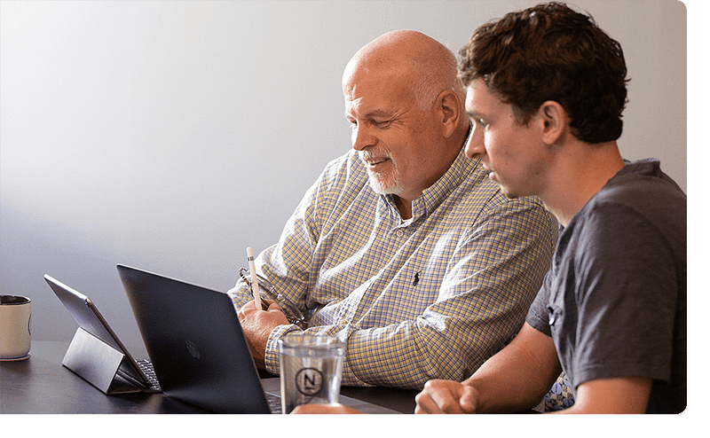 Two employees look at their laptop together.