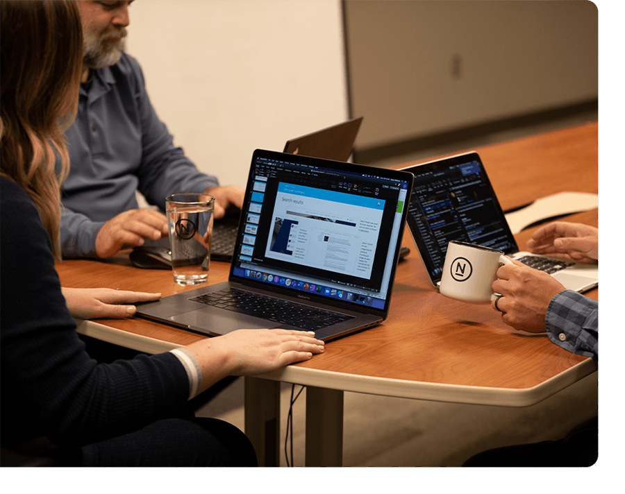 A Ntara team working on laptops together in a conference room.