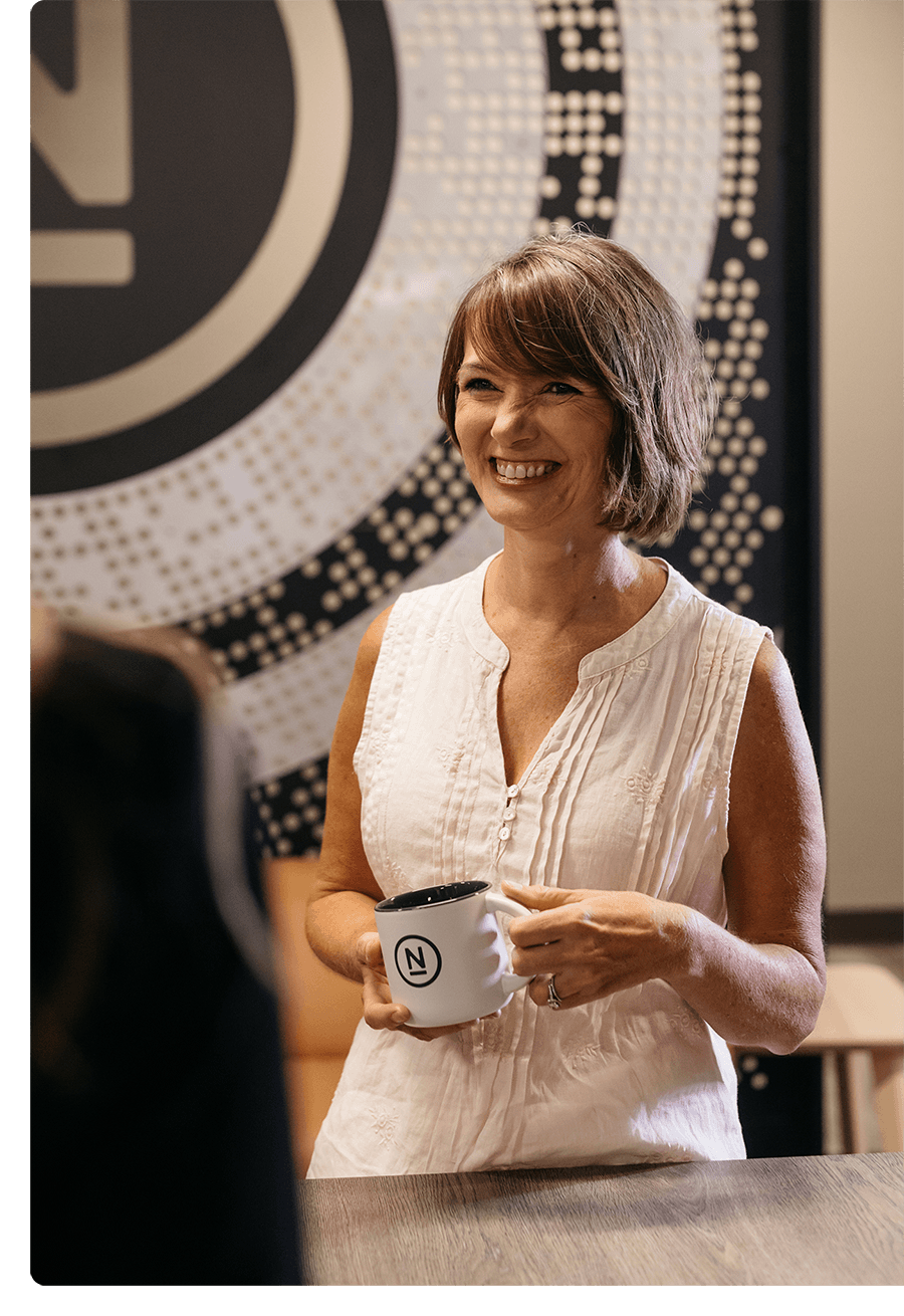 Woman with short brown hair smiling, holding a coffee cup, talking to coworkers