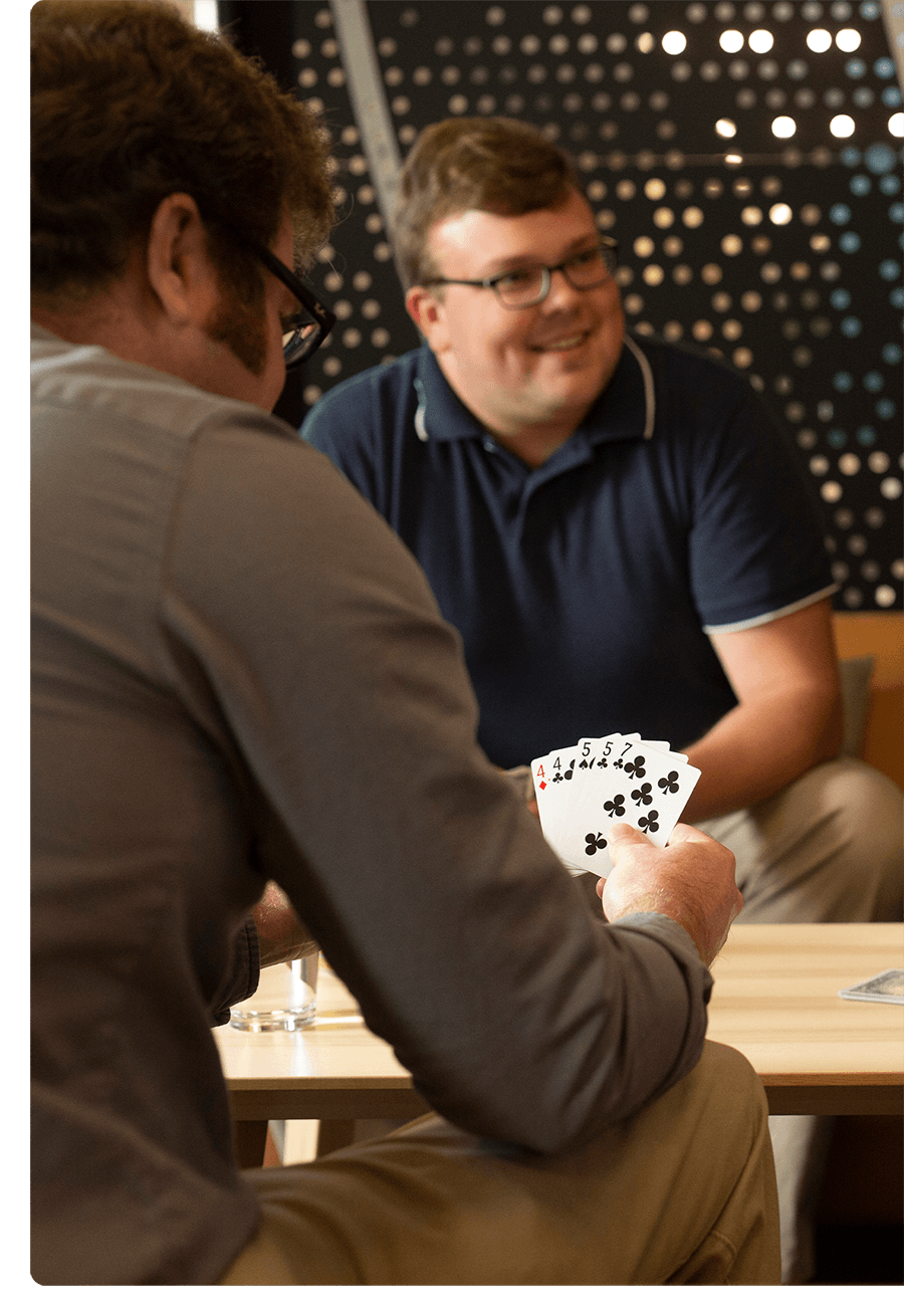 Two coworkers smile and laugh over a game of cards.
