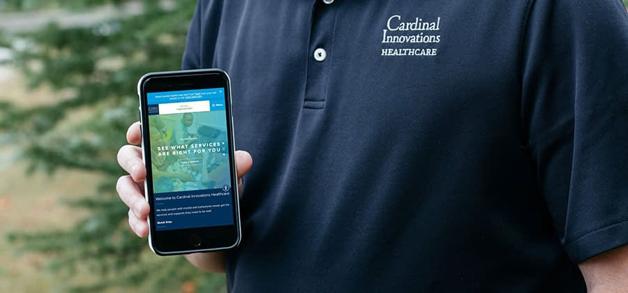 A cropped image of a man holding a mobile phone with the Cardinal Innovations website pulled up.