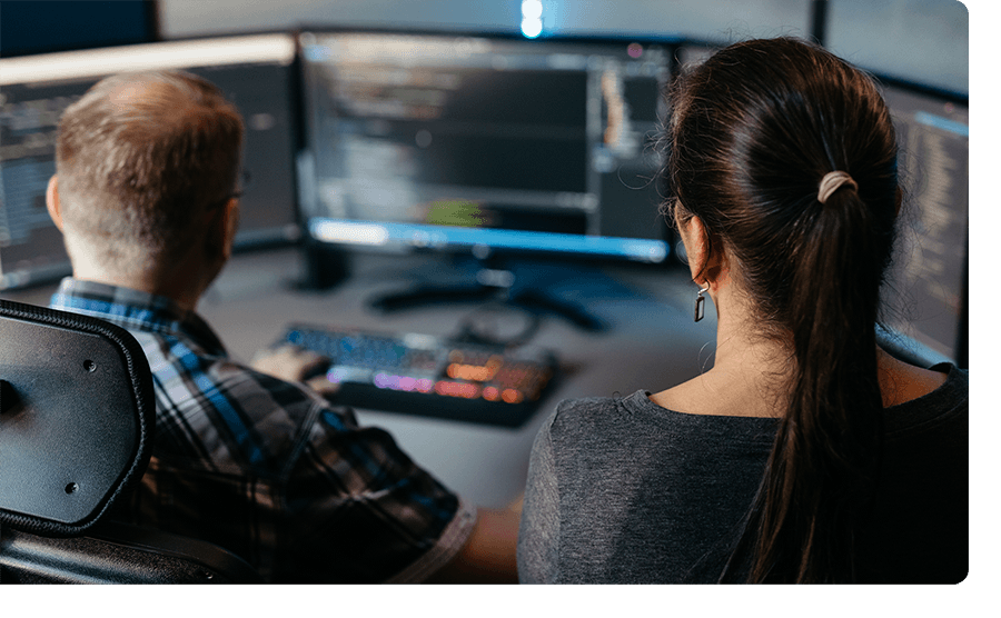A woman looking over the shoulder of a male developer.