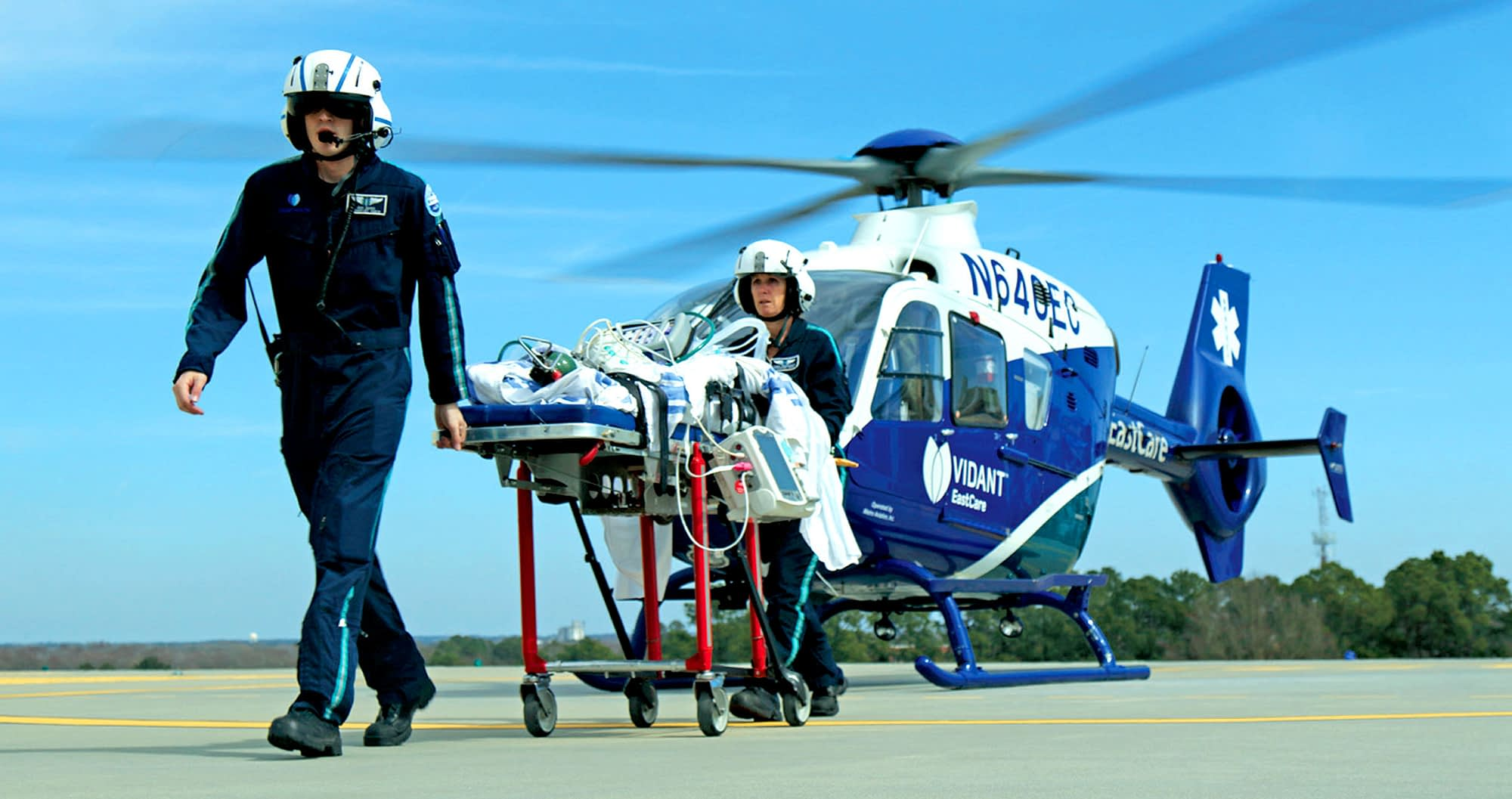 Two emergency response crewmen take a patient off a helicopter and walk towards hospital.