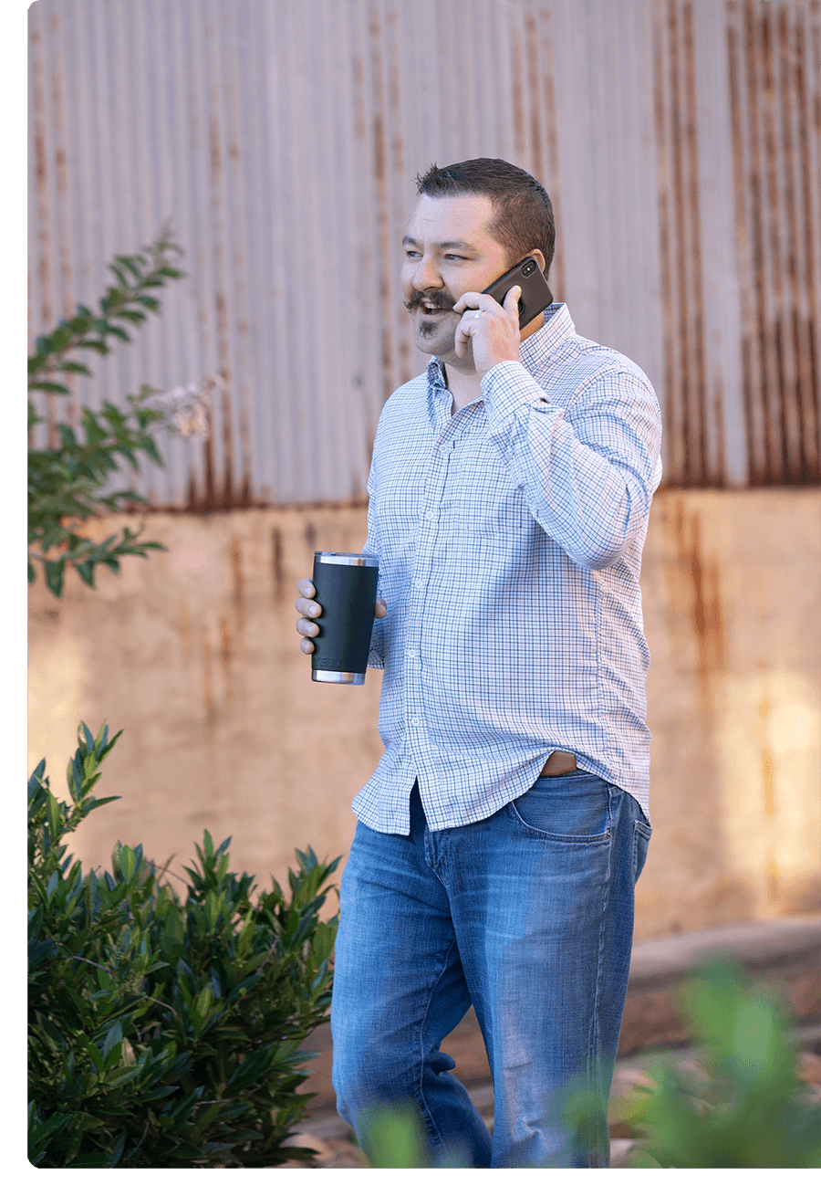 Man with large mustache in blue long-sleeve shirt, holding coffee, stands and talks on his cell phone.