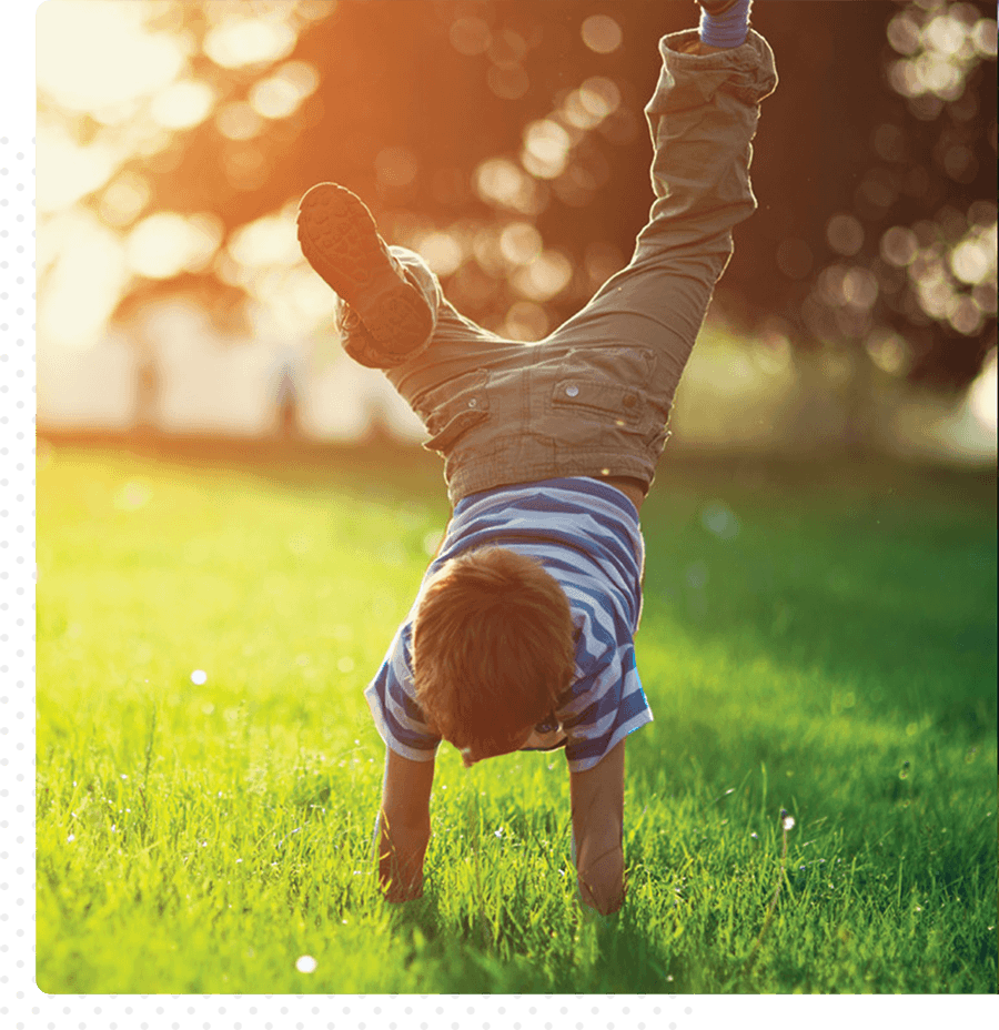 A small child plays outside in the grass. He is doing a handstand.