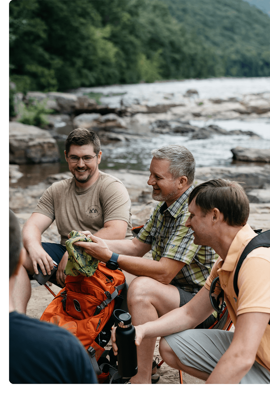 Three men hanging together outside on a camping trip