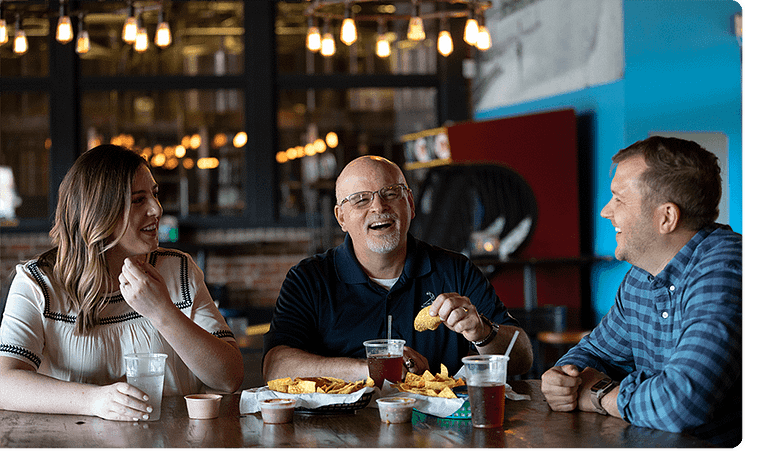 Three Ntara employees laugh together at a meal. Laughing and enjoying each other's company.