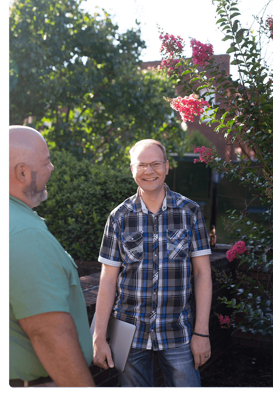Two men stand outside talking. There is a tree with pink blooms behind them.