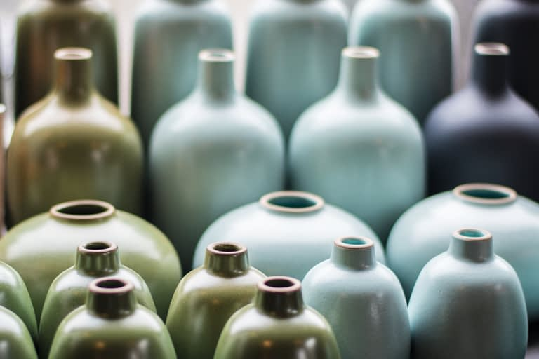 Green, light blue, and black ceramic pottery, neatly arranged by color.