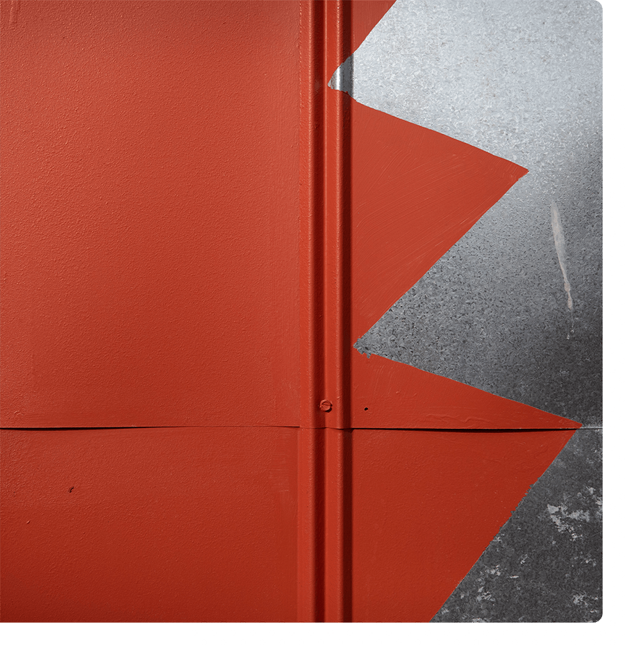 An abstract close-up of a red wall with a silver zig zag pattern on the right.