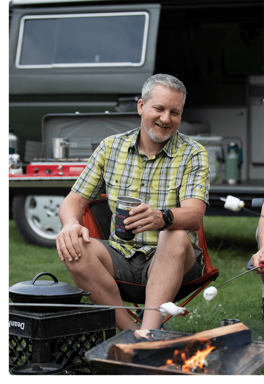 Man with gray hair and goatee sits at a campsite holding his coffee.