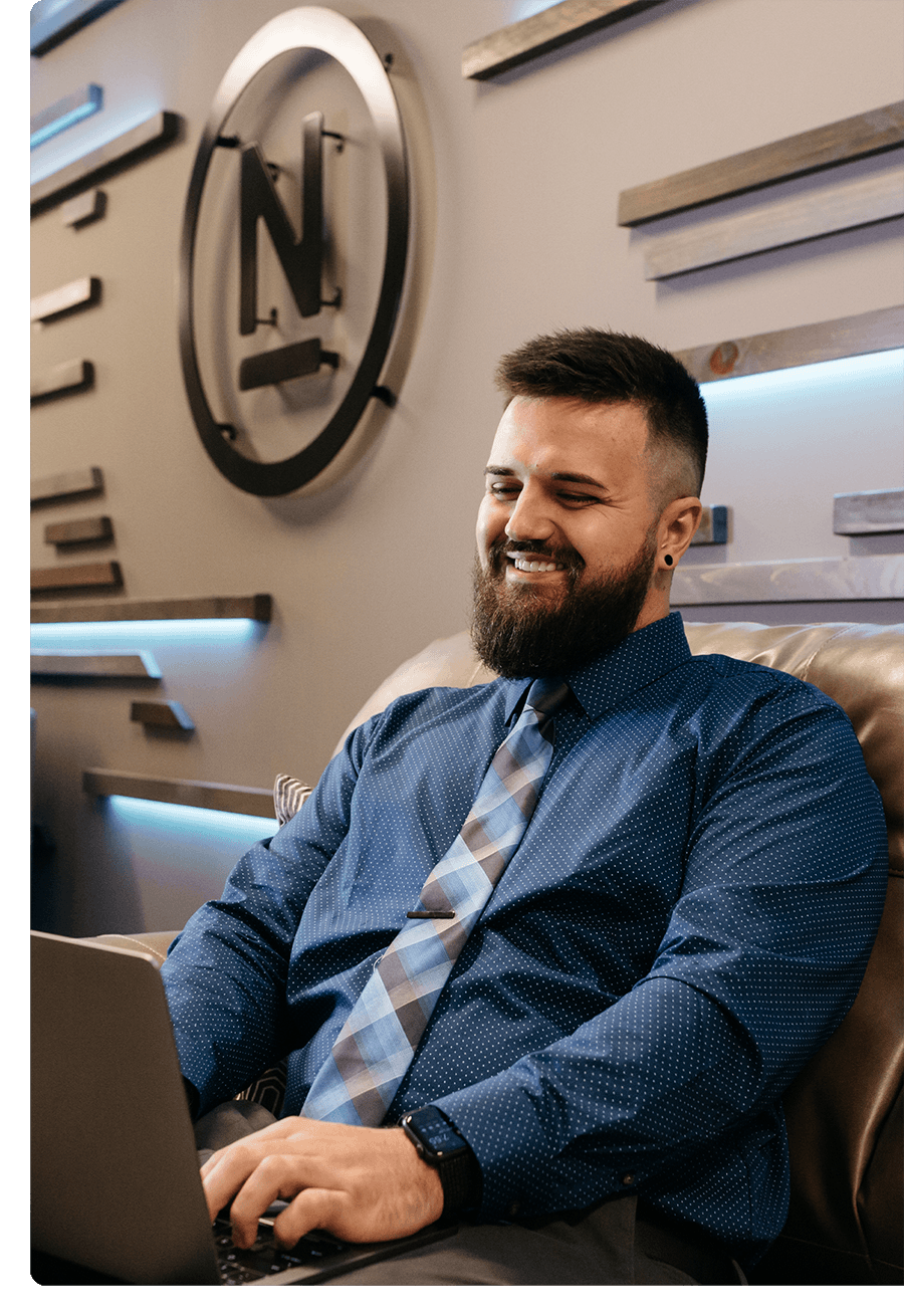 Man with a beard in a dress shirt and tie smiling while working on a laptop.