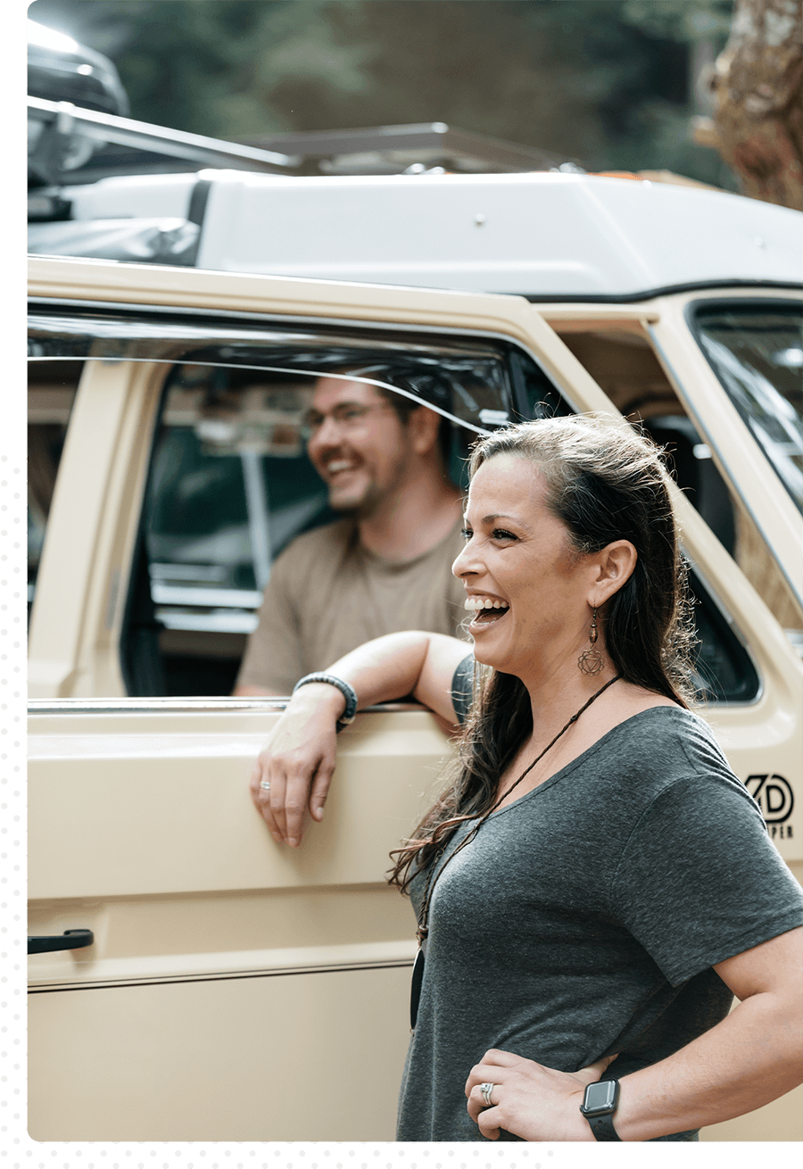 A laughing woman with her arm on the window of a van with a man inside.