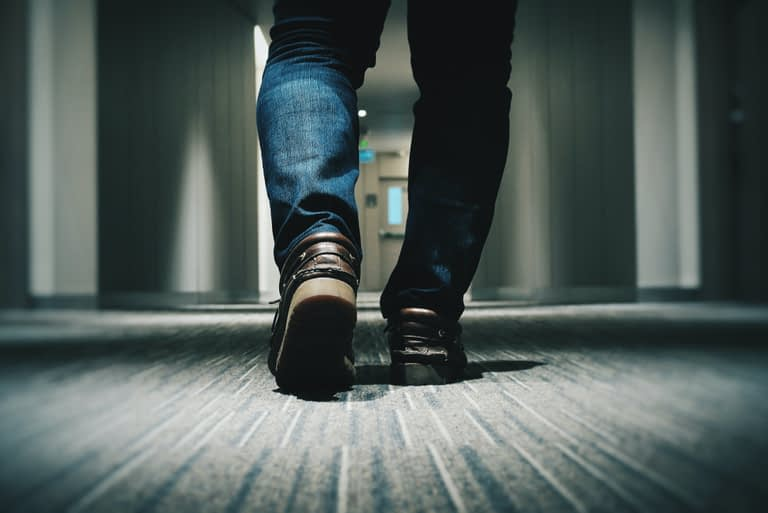 A close up view of a man in jeans and brown loafers walking down an office hallway.