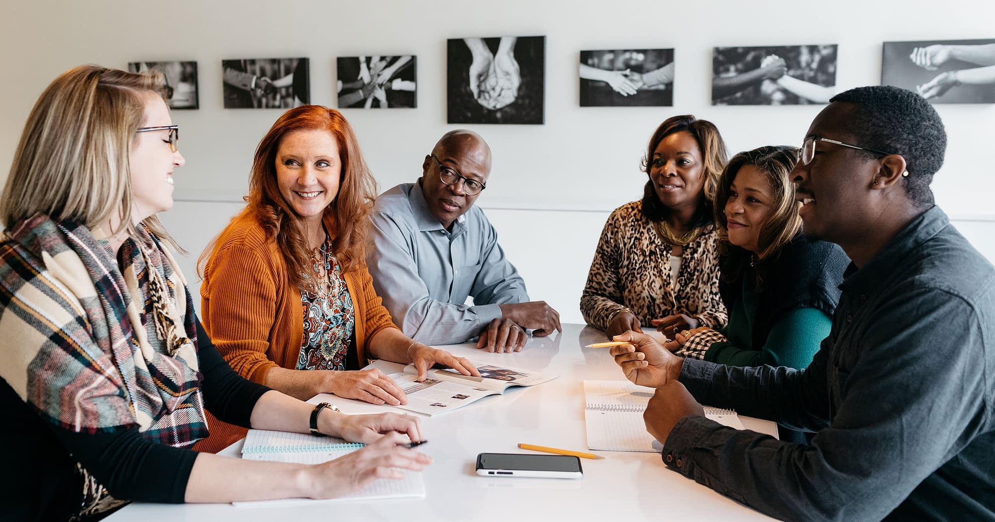 Four people working together at a white table.