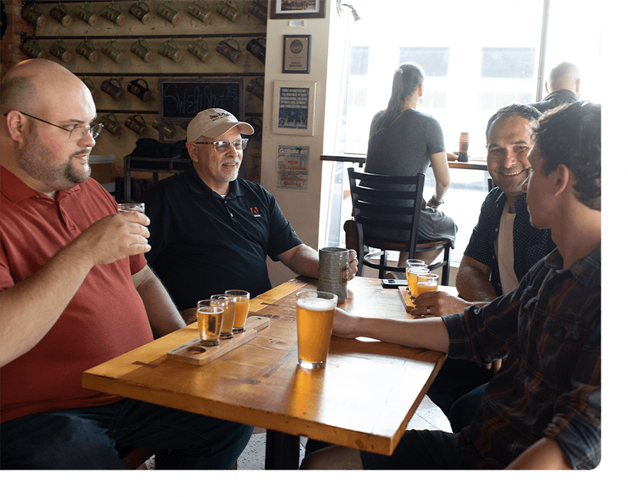 Four coworkers enjoy beers and food after work.