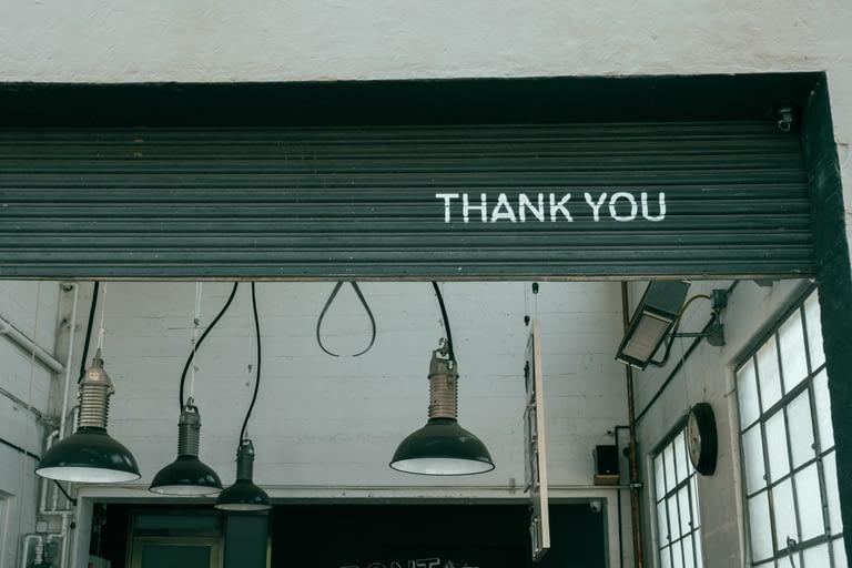 "A warehouse garage door is rolling up. The bottom of the door says, ""Thank you""."