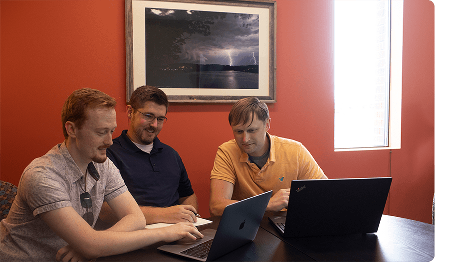 Three men in polos working on laptops in an orange room.